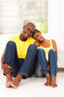 young african couple sitting on the bedroom floor