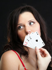 woman holding playing cards black background