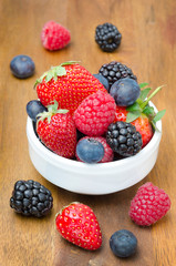 Fresh berries in a bowl on a wooden background