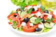 Greek salad with feta cheese, olives and vegetables on white