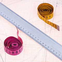 Pink and yellow measure tapes and metal ruler
