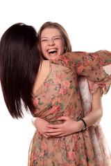 Two teenage girls hugging and laughing
