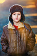 sunlight boy in brown jacket and fur hat on street on blue abstr