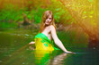sunlight Blond young woman standing waist water in the river in