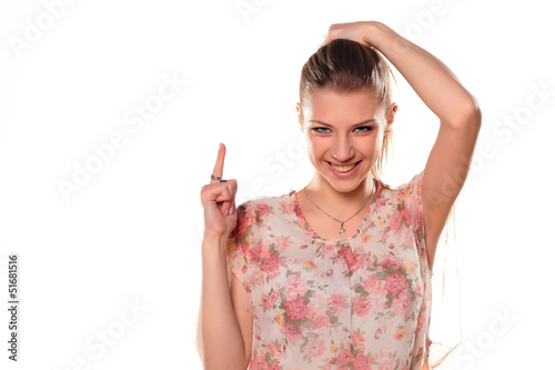 teenage girl in dress pointing a finger at a blank