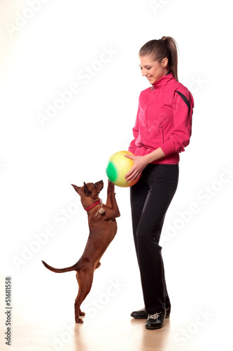 teenage girl in tracksuits playing with a dog and a ball