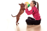 girl in tracksuits playing with a dog and a ball