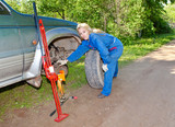 woman in working overalls tries to replace wheel an off-road car
