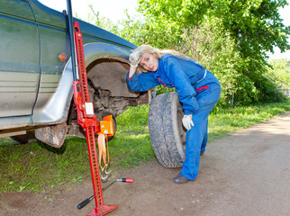 The woman in working overalls tries to replace a wheel