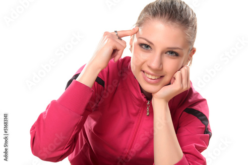 smiling teenager girl in a tracksuit points a finger at her head