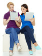 Two girls learning together with touchpad for school