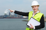Female supervisor pointing to industrial site poster