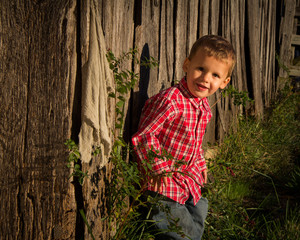Young Boy Next to Rustic Wood