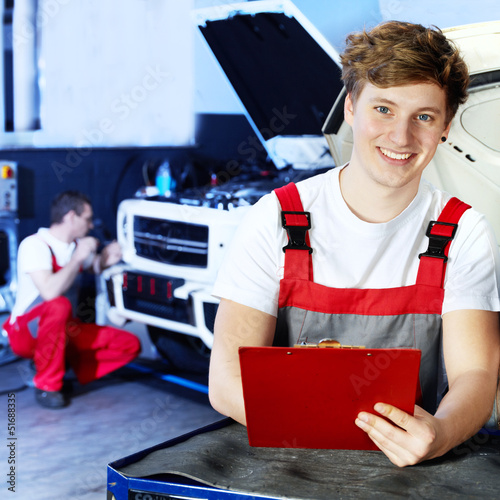 Apprentices for car mechanic is satisfied with his job