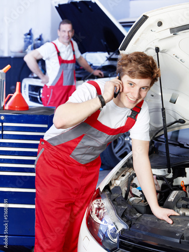 Car mechanic is satisfied with his job calling a customer