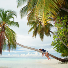 Happy woman lying upon palm tree on the beach