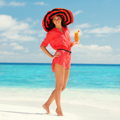 Fashion woman drinking cocktail on the beach