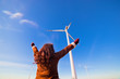 Happy woman with hands up looking at eco wind turbines