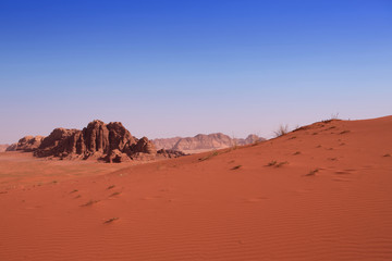 A red sand dune with a rock background in Wadi Rum desert