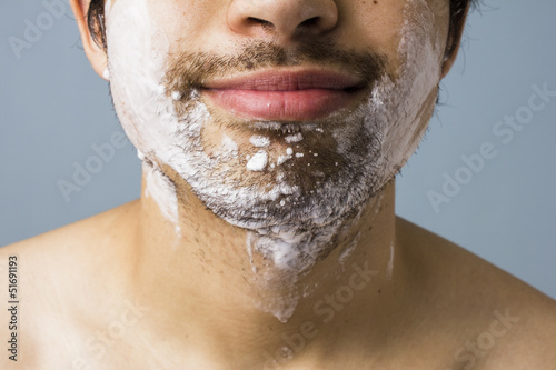 Young man's chin covered in shaving foam