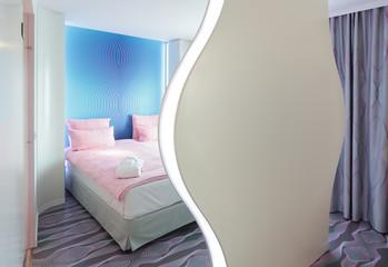 Hotelbett vor weissem Raumteiler blanko