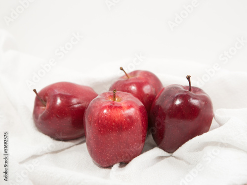 Group of ripe, red gala apples on towel indoors