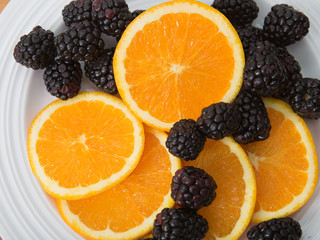 Plate of sliced navel oranges and fresh blackberries
