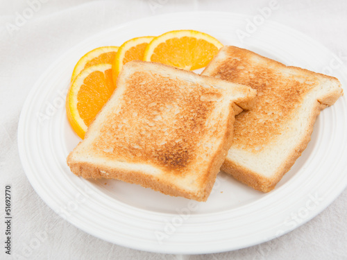 Unbuttered toast on white plate garnished with orange slices