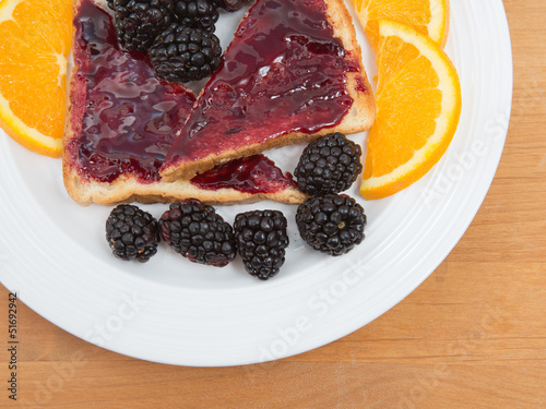 Plate of sliced toast with preserves blackberries and oranges