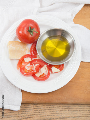 Plate of vine ripened red tomato with parmesan and olive oil