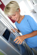 Young boy drinking water from fridge