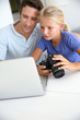 Father and daughter looking at digital camera and laptop