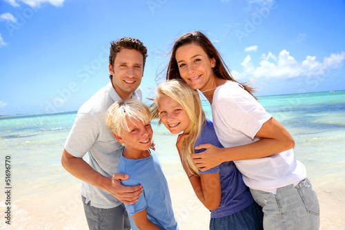 Happy couple with kids at the beach