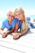 Blond teenagers laying on pool deck in summer