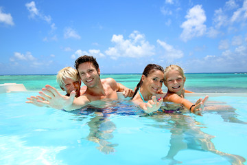 Family of four bathing in swimming pool