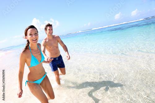 Leinwanddruck Bild Couple running on a sandy beach