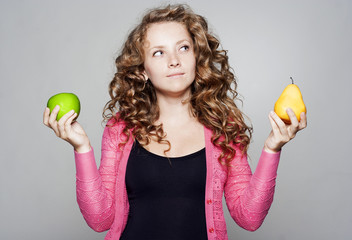 Young pretty woman holding an apple and a pear