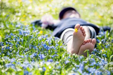 Mädchen liegt in einer blauen Blumenwiese