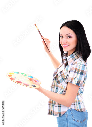 Beautiful young woman painter with brushes and palette at work,