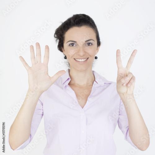 Geschäftsfrau zeigt mit sieben Fingern die Zahl 7 an