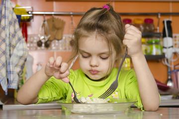 Четырехлетняя девочка ест вилкой и ложкой сидя за столом