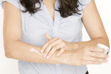 Frau träft Creme auf Arm auf