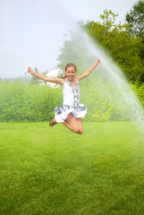 Girl jumps under spray drops