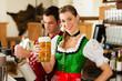 Junger Mann in Tracht zapft ein Bier im Restaurant