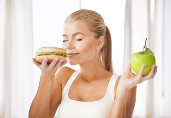 woman smelling hamburger and holding apple