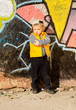 Confident little boy posing in front of graffiti