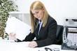 Blonde Frau am Schreibtisch im Büro blätter durch Dokumente