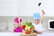 Cheerful chef kids in kitchen