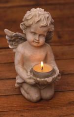 Engel mit Kerze vor Holzhintergrund