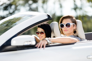 Close up of girls wearing sunglasses in the car